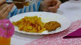 De tiener eet frietenaardappel en lapje vleesplaat met persoonskoffie in restaurant stock footage