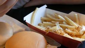 De tiener eet gebraden frieten met uien en kaas De hand vernietigt een plastic vork met ongezond voedsel of snel stock video