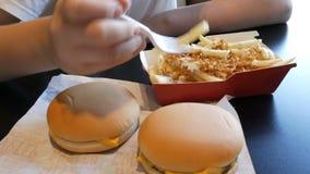 De tiener eet gebraden frieten met uien en kaas De hand vernietigt een plastic vork met ongezond voedsel of snel stock footage