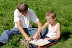 De tiener en het Jonge geitje lezen Boek Stock Fotografie