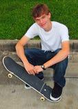 De tiener en zijn skateboard in toevallig stellen stock afbeeldingen