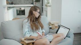 De tiener in glazen op laptop worden gelezen, die het scherm bekijken, schrijft in notitieboekje, voorbereidingen treffend voor e stock video