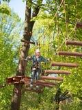 De tiener in helm en met een jongen van de veiligheidskabel gaat op hangbrug wordt gemaakt van het programma opent de vage achter Stock Foto's