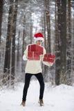 De tiener in hoed Santa Claus verzamelt giften binnen in een sneeuwbos Royalty-vrije Stock Afbeelding