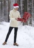 De tiener in hoed Santa Claus verzamelt giften binnen in een sneeuwbos Royalty-vrije Stock Foto's