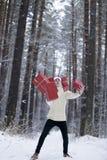De tiener in hoed Santa Claus verzamelt giften binnen in een sneeuwbos Royalty-vrije Stock Fotografie