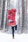 De tiener in hoed Santa Claus verzamelt giften binnen in een sneeuwbos Stock Afbeeldingen