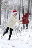 De tiener in hoed Santa Claus verzamelt giften binnen in een sneeuwbos Stock Fotografie