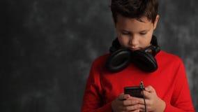 De tiener in de hoofdtelefoons zoekt iets in zijn telefoon stock videobeelden