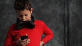 De tiener in de hoofdtelefoons zoekt iets in zijn telefoon stock video