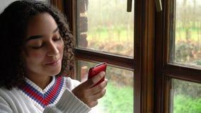 De tiener jonge vrouw die van het Biracial Afrikaanse Amerikaanse meisje haar mobiele celtelefoon of smartphone voor sociale medi stock videobeelden