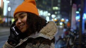 De tiener jonge vrouw van het Biracial Afrikaanse Amerikaanse meisje op stedelijke stadsstraat die bij nacht op mobiele celtelefo stock videobeelden