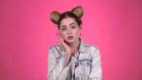 De tiener kijkt verrast vooruit kijkt Roze achtergrond Langzame Motie stock footage
