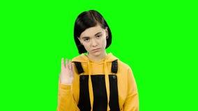 De tiener kijkt vooruit boos Het groene scherm stock videobeelden
