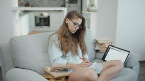 De tiener leest op laptop, schrijft in notitieboekje, voorbereidingen treffend voor examens of thuiswerk, partij van boeken stock video