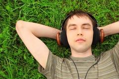 De tiener ligt op gras in hoofdtelefoons Royalty-vrije Stock Foto's