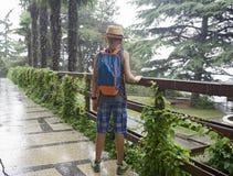 De tiener met een rugzak kost onder een de zomerregen Stock Afbeeldingen