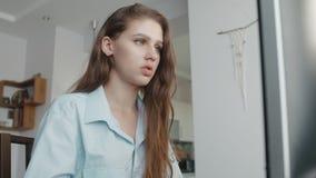 De tiener met lang haar bekijkt het type van monitorscherm op computertoetsenbord, voorbereidingen treffend voor thuiswerk stock footage
