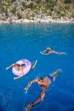 De tiener met ouders baadt in blauw water van Middellandse-Zeegebied Stock Foto's