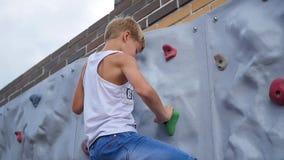 De tiener onderaan de muur voor het beklimmen Sporten in openlucht stock footage