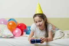 De tiener` s verjaardag is 10-11 jaar oud Een meisje in een feestelijke hoed ligt met een gift op het bed Royalty-vrije Stock Fotografie