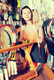 De tiener selecteert een nieuwe racket voor badminton royalty-vrije stock foto