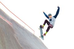 De tiener skateboarder in GLB doet een truc met een sprong op de helling in skatepark Geïsoleerde schaatser en helling  stock fotografie