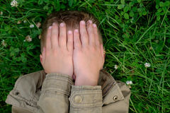 De tiener sluit zijn ogen met handen Stock Foto's