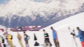 De tiener snowboarder rit op springplank werpt sneeuwbal in mand Mensen zonnig stock footage