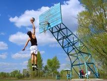 De tiener speelt basketbal Stock Afbeelding