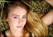 De tiener van de blonde in gras Stock Afbeeldingen