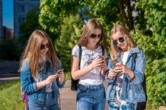 De tiener van het drie meisjesschoolmeisje, die jeanskleren en zonnebril dragen In de handen van het houden van mobiele telefoons royalty-vrije stock foto's