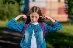 De tiener van het meisjesschoolmeisje De zomer in aard De oren van de vingersdekking Het concept hoort zeer luid om het even wat  stock foto