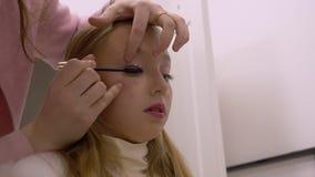 De tiener van het portretmeisje terwijl het toepassen van mascara op wimpers in make-upstudio stock videobeelden