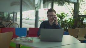 De tiener werkt met laptop in de bibliotheek stock videobeelden
