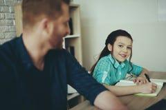 De tienerdochter doet thuis thuiswerk stock foto