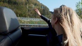 De tienergolven haar dienen de wind in convertibel in stock footage