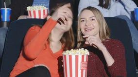 De tienerjaren zijn gekauwde popcorn met soda en genieten van films stock videobeelden