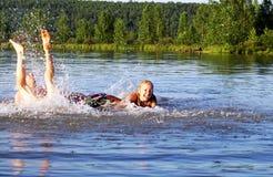 De tienerjaren zwemmen en spelen op de lach bij een rivier Royalty-vrije Stock Afbeelding