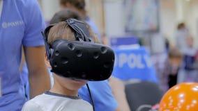De tienerjongen die virtuele werkelijkheidshoofdtelefoon met behulp van bij technologie toont stock videobeelden