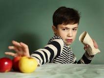 De tienerjongen eet fastfood het fruit van het broodjesafval stock afbeeldingen
