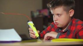 De tienerjongen gebruikt een 3D pen Hij creeert een 3D cijfer van plastiek stock footage