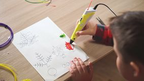 De tienerjongen gebruikt een 3D pen Hij creeert een installatieblad van rood ABS plastiek stock footage