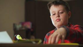 De tienerjongen gebruikt een 3D pen Hij gaat een 3D cijfer van plastiek tot stand brengen stock video
