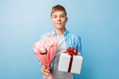 De tienerjongen geeft een gift en bloemen, een mens in liefde, op een blauwe achtergrond stock foto's
