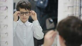 De tienerjongen kiest nieuwe oogglazen in optica stock footage