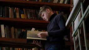 De tienerjongen leest een boek in de bibliotheek tegen een achtergrond van boekenrekken met heel wat boeken stock footage