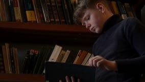 De tienerjongen leest een boek in de bibliotheek tegen een achtergrond van boekenrekken met heel wat boeken stock video