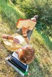 De tienerjongen ligt en leest boek Royalty-vrije Stock Foto