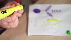 De tienerjongen neemt een stuk van geel ABS plastiek in een 3D pen op Hij creeert een plastic 3D cijfer stock video